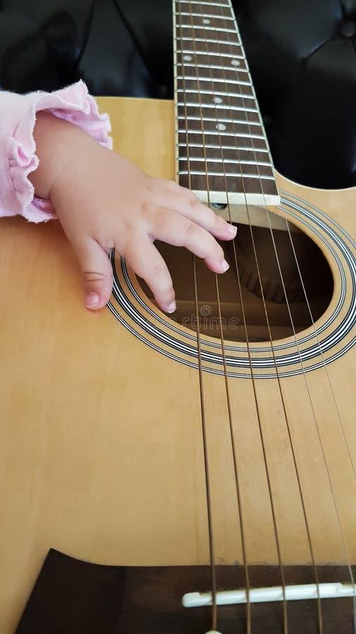 Guitare apprenant des doigts de bébé de fond photo libre de droits