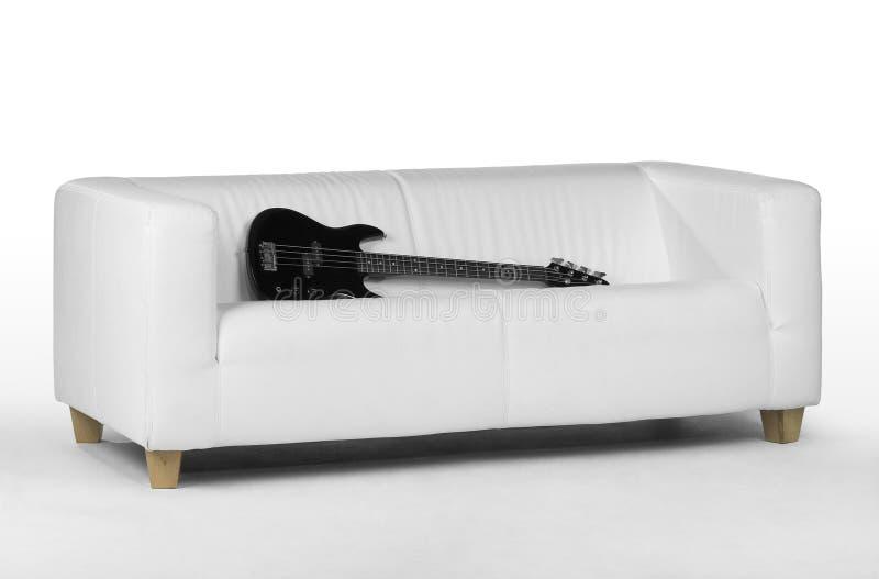 Guitare basse noire sur le divan blanc images stock