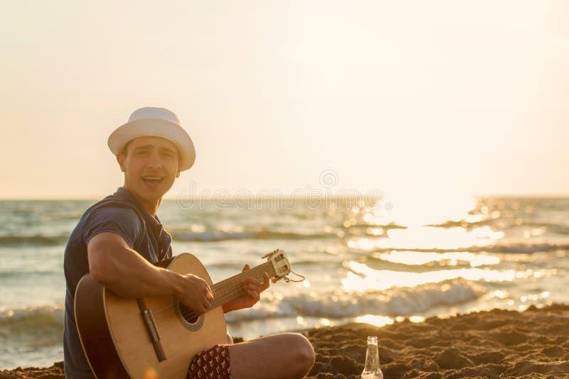 Guitare de jeu de jeune homme sur la plage et apprécier dans le coucher du soleil photos libres de droits
