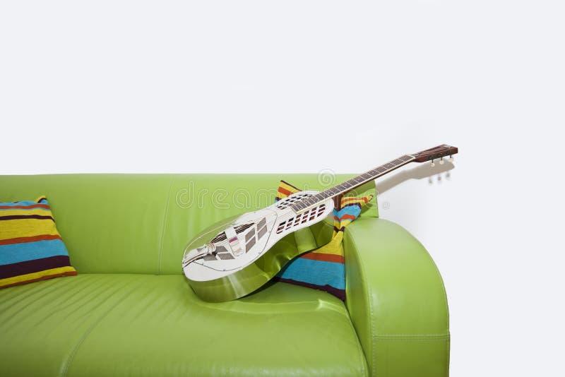 Guitare de résonateur sur un sofa vert photographie stock libre de droits