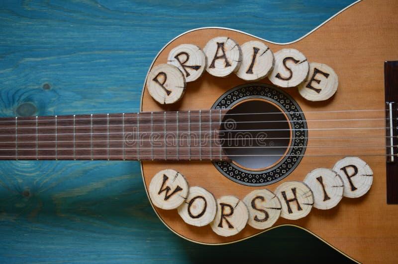 Guitare sur le bois avec des mots : ÉLOGE et CULTE photo stock