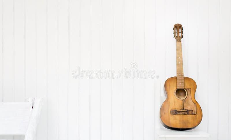 Guitare sur une chaise blanche et un fond blanc photos stock