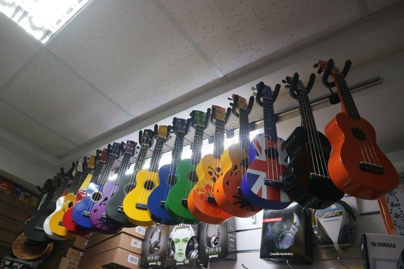 Guitares multicolores d'ukulélé dans un magasin d'instrument de musique photo stock