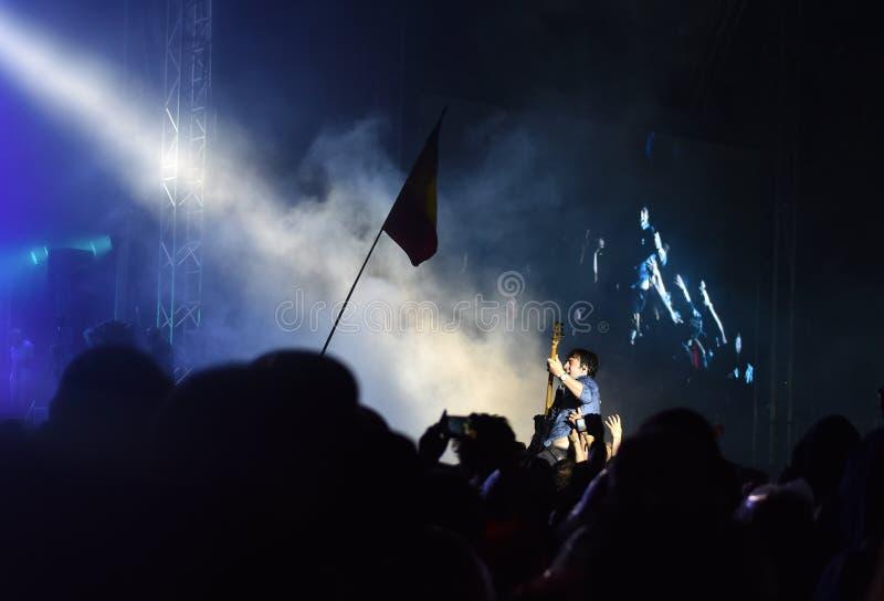 Guitarist crowd surfing during a concert. BONTIDA, ROMANIA - JULY 15, 2016: Bass guitarist Chris Batten from Enter Shikari British rock band crowd surfing during royalty free stock images