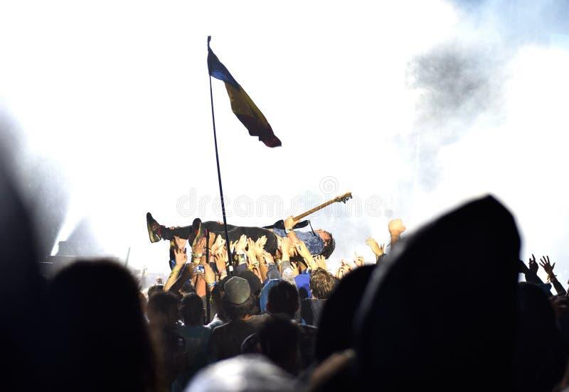 Guitarist crowd surfing during a concert. BONTIDA, ROMANIA - JULY 15, 2016: Bass guitarist Chris Batten from Enter Shikari British rock band crowd surfing during royalty free stock photo