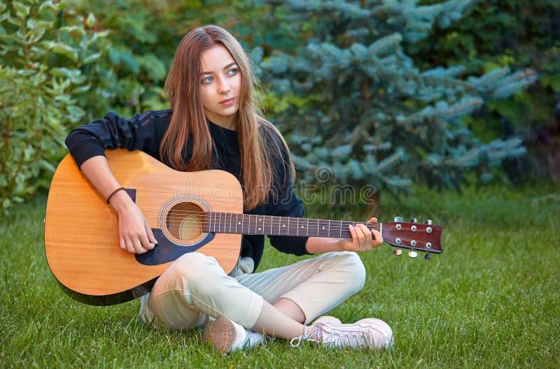 Guitarist girl play music on guitar. Beautiful singer royalty free stock image