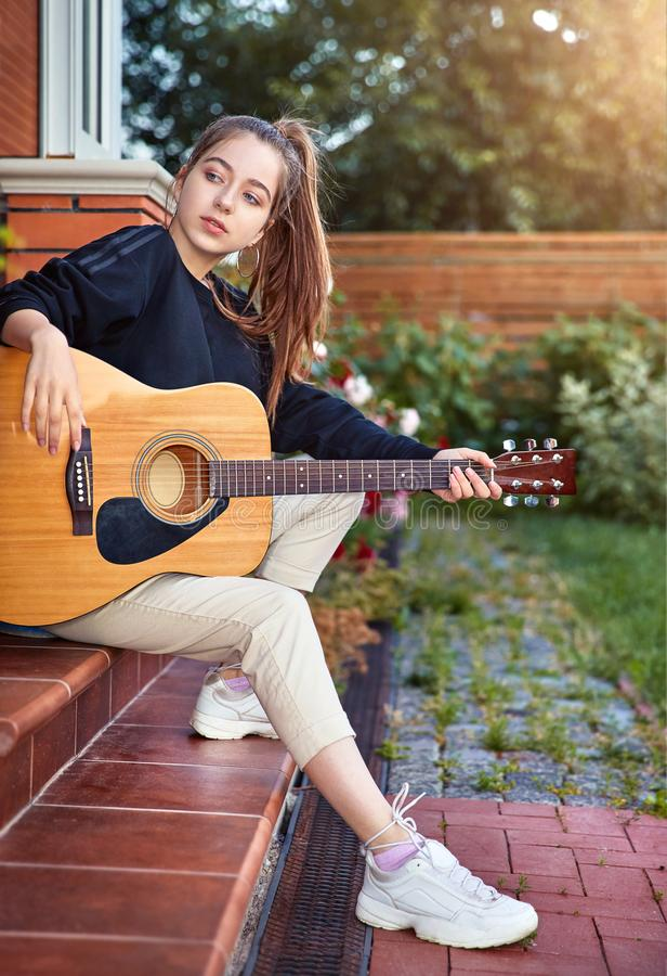 Guitarist girl play music on guitar. Beautiful singer stock images