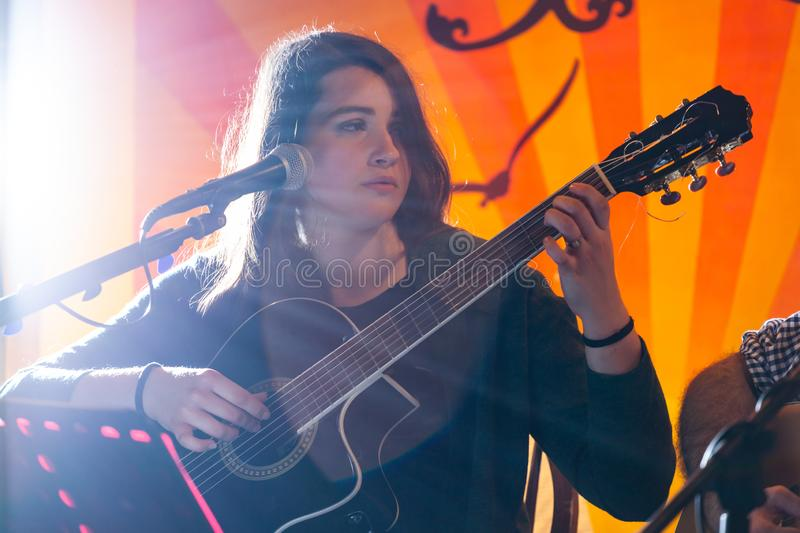 Guitarist during a musical performance. Portrait of a young guitarist during a musical performance royalty free stock images