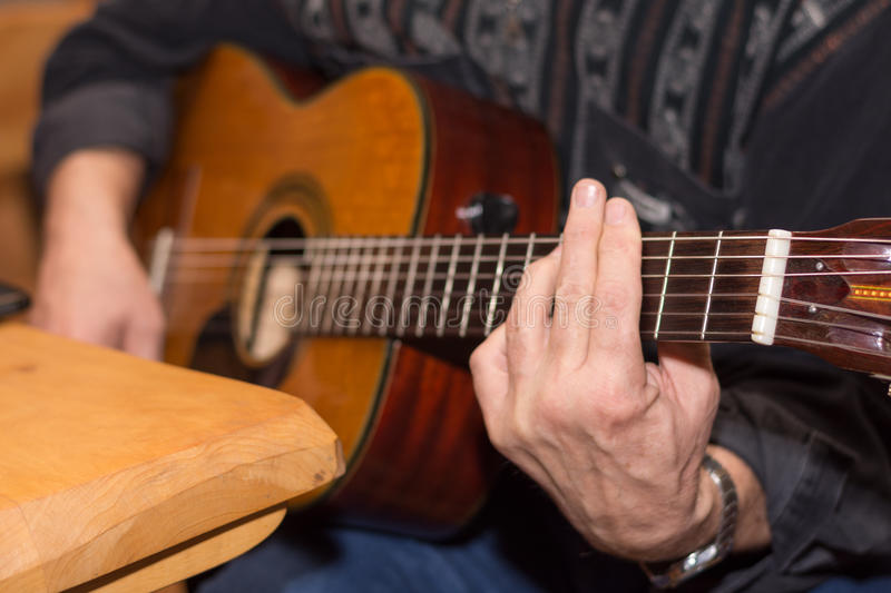 Guitarist playing accoustic guitar. Blured image stock images