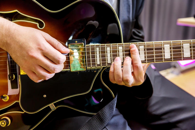 Guitarist playing in jazz band. Hands guitarist playing chords in jazz band closeup stock photos