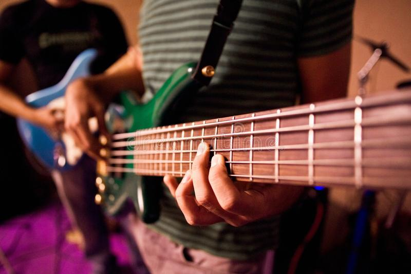 Guitarist playing the notes of a bass during a rehearsal, close-up stock photography