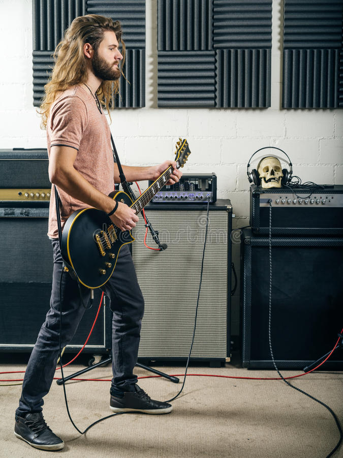 Guitarist playing in the recording studio. Photo of an attractive man playing electric guitar in a recording studio royalty free stock image