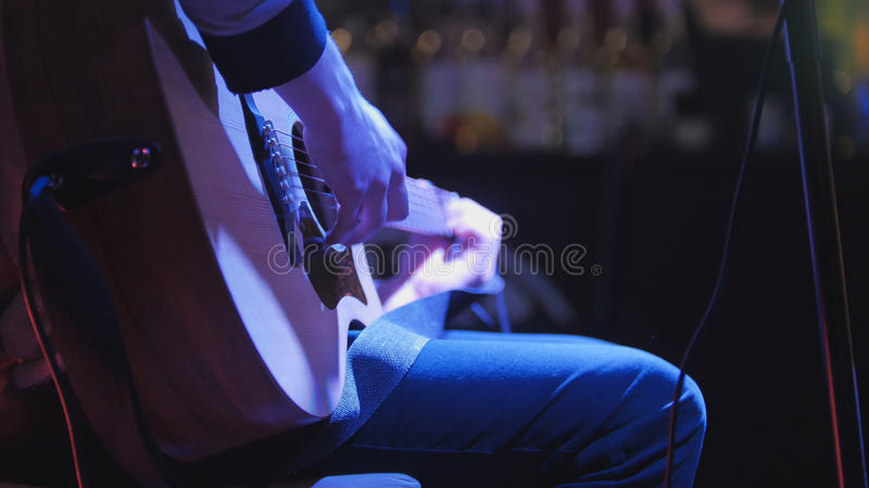 Guitarist plays concert acoustic guitar in night club. Telephoto stock photo