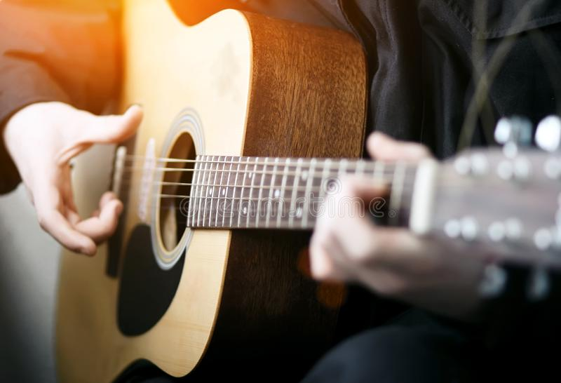 The guitarist plays a melody on a wooden acoustic guitar stock photos