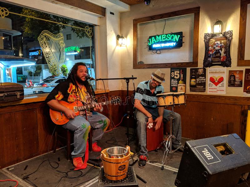 Guitarist Reggae Musician Keith Batlin sings and plays with drummer royalty free stock photo
