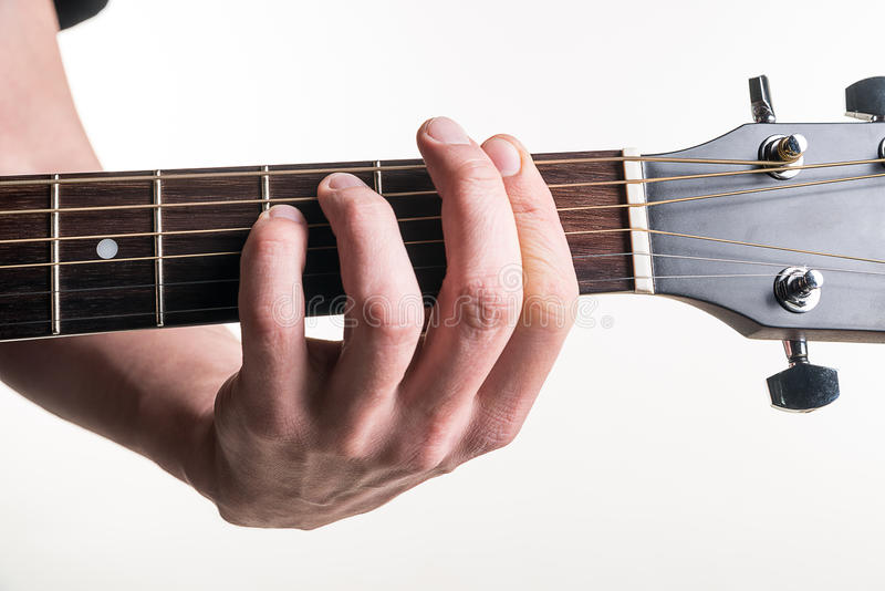 The Guitarists Hand Clamps The Chord Fm On The Guitar On A White