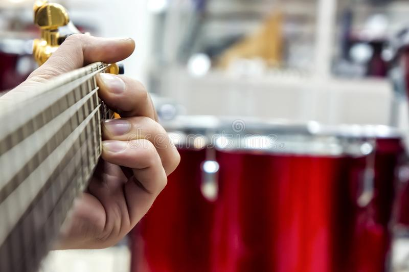The guitarist`s hand, close-up and soft focus, takes the akrod on a guitar fretboard, against the background of the drum set. stock photos