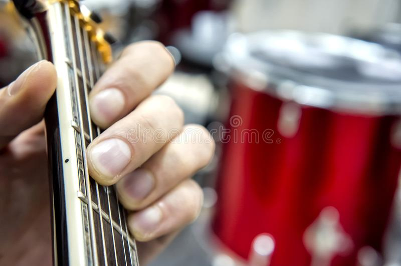 The guitarist`s hand, close-up and soft focus, takes the akrod on a guitar fretboard, against the background of the drum set. royalty free stock photo