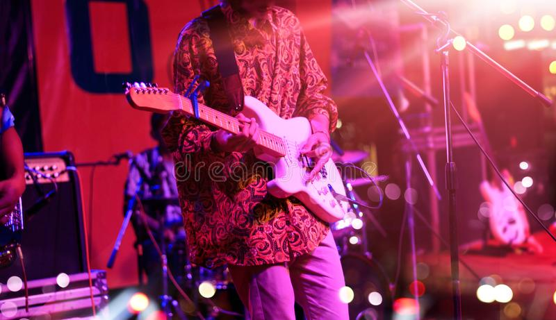 Guitarist on stage with red lighting for blackground. royalty free stock photos