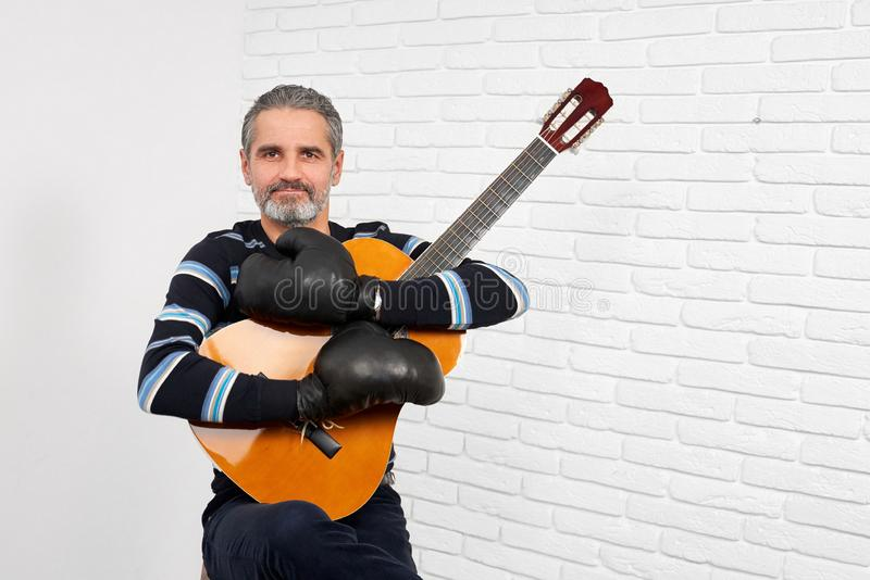 Guitarist wearing in boxing gloves posing. royalty free stock image