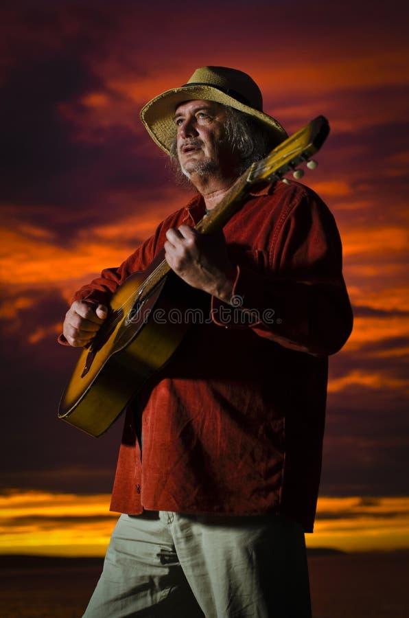 Guitariste de coucher du soleil avec l'éclairage excessif photos libres de droits