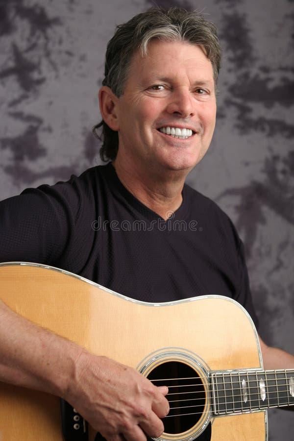 Guitariste mâle mûr photo stock