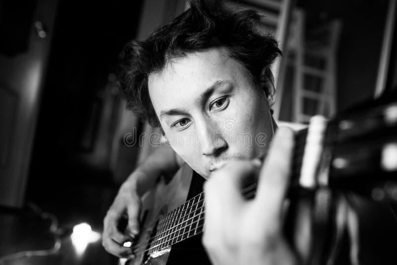 Guitariste passionné fou jouant la guitare, portrait en gros plan noir et blanc Musicien avec les cheveux en désordre images stock
