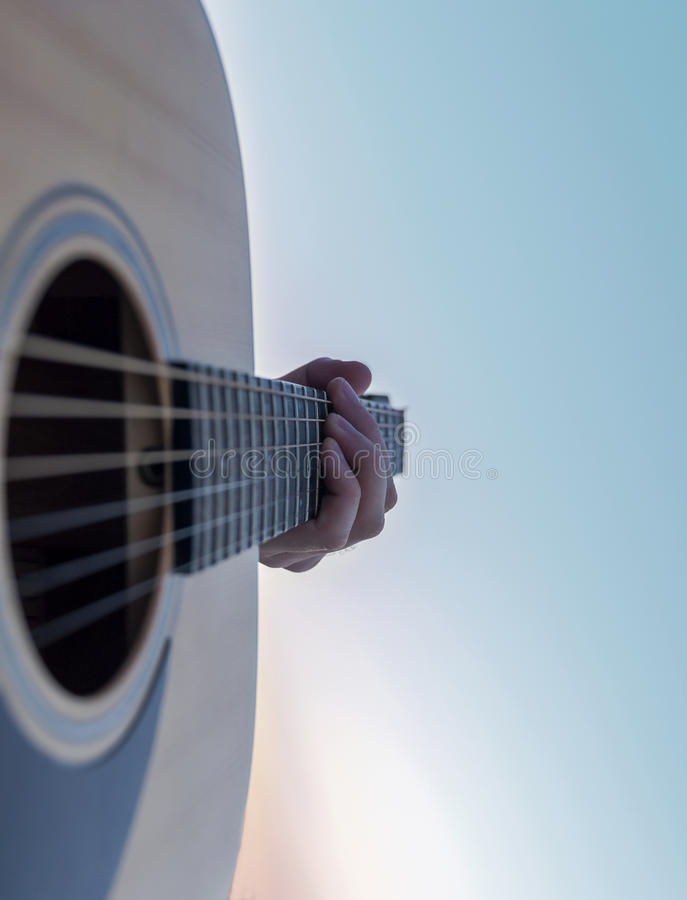 Guitariste Playing sur la guitare acoustique au coucher du soleil pourpre au lac photographie stock libre de droits