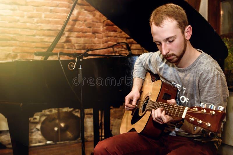 Guitariste solo élégant exécutant sur un concert sur un fond o images stock