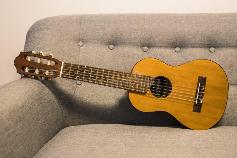 Guitarlele sul sofà immagine stock libera da diritti