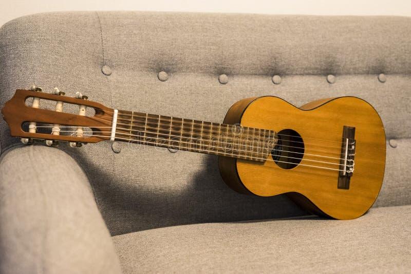 Guitarlele sul sofà immagine stock