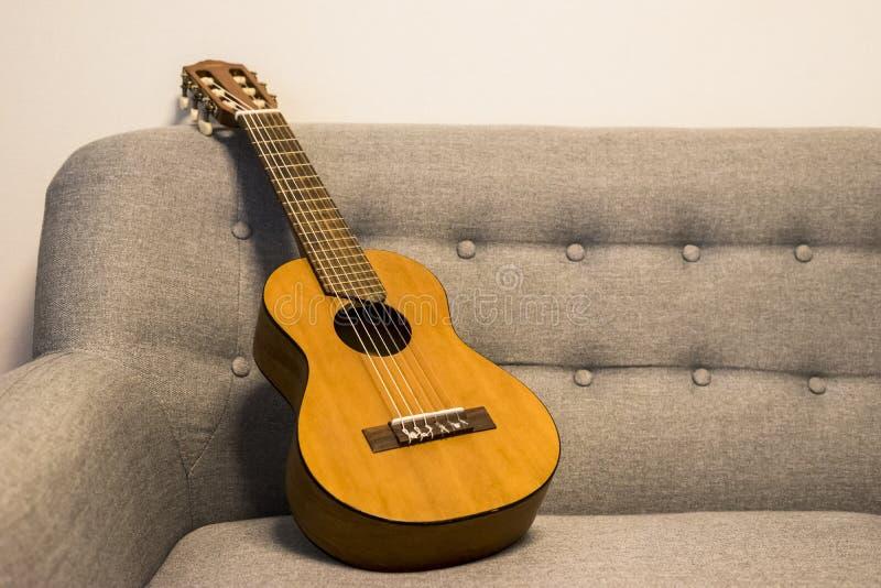 Guitarlele sul sofà fotografia stock libera da diritti