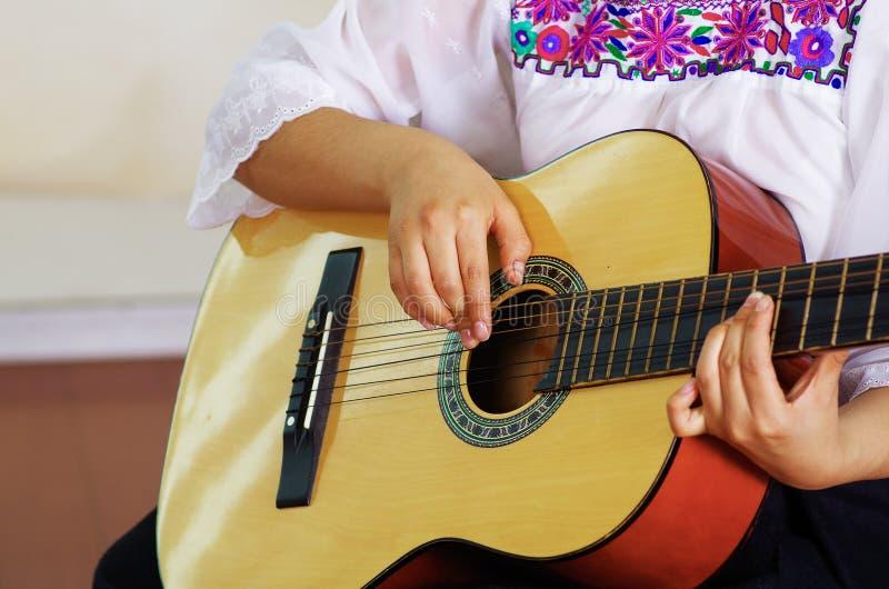 Guitarra acústica bonita do close up que está sendo jogada pela mulher latino-americano que senta-se para baixo, conceito do músi imagem de stock royalty free