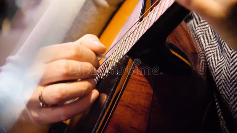 Guitarra acústica bonita do close up que está sendo jogada pela mulher que senta-se para baixo, conceito do músico Mulher que jog foto de stock royalty free