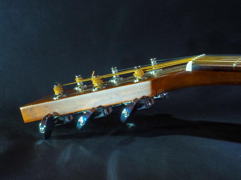 Guitarra acústica clássica de instrumento musical da cor clara com pinos de aço e cordas de prata em um fundo escuro imagens de stock royalty free