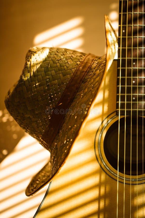 Guitarra acústica com o chapéu no fundo claro imagens de stock