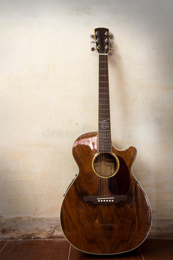 Guitarra acústica com a parede da textura do grunge fotografia de stock