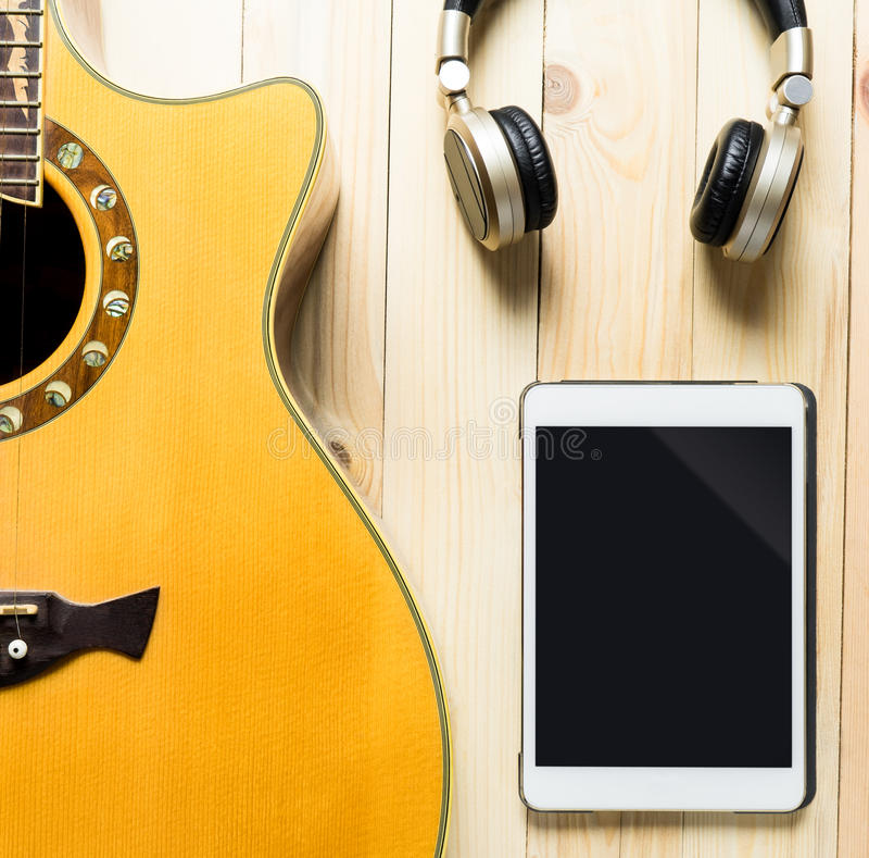 Guitarra acústica con el auricular y la tableta para la música fotos de archivo libres de regalías