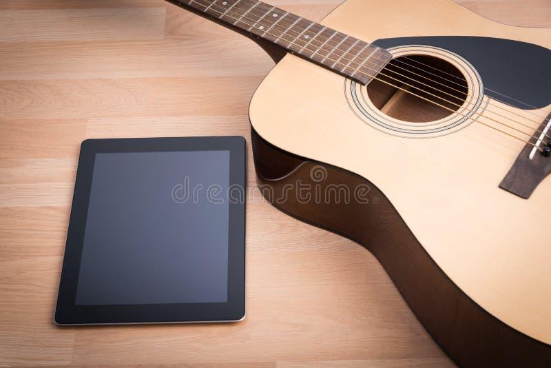 Guitarra acústica con la tableta digital foto de archivo