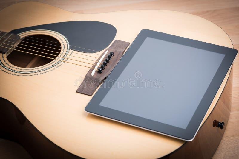 Guitarra acústica con la tableta digital fotografía de archivo libre de regalías