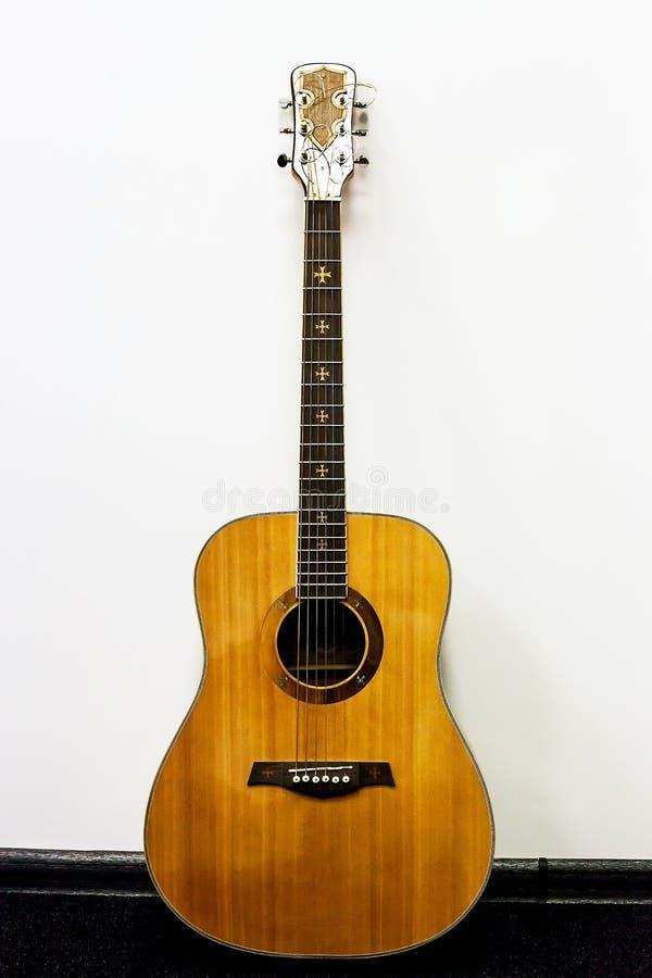 Guitarra acústica de madeira clássica do vintage velho perto da parede fotografia de stock royalty free