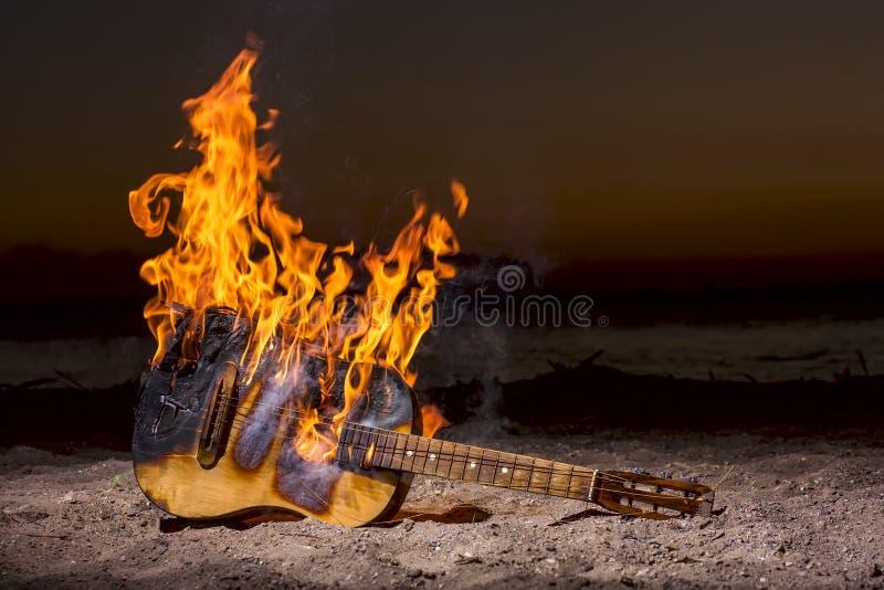 Guitarra acústica de madeira no fogo imagens de stock