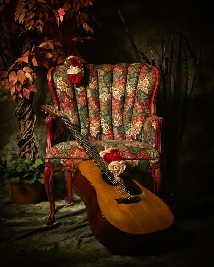 Guitarra acústica do vintage que inclina-se contra a cadeira antiga imagens de stock royalty free