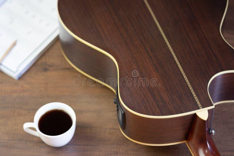 Guitarra acústica e para escrever notas musicais e xícara de café na tabela de madeira foto de stock