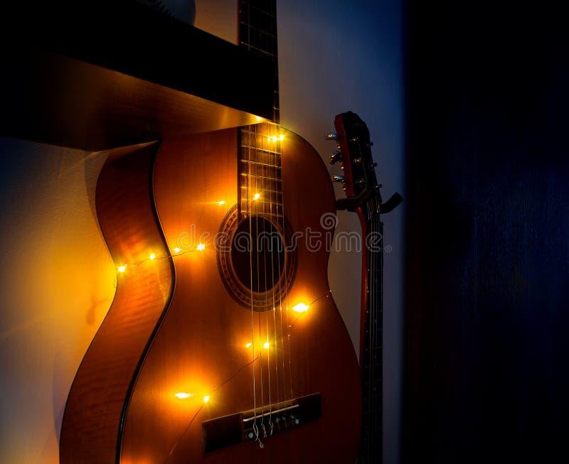 Guitarra acústica en la ejecución del sitio en la pared en un estante con una guirnalda, interior del sitio, afición casera fotos de archivo