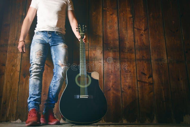 Guitarra acústica en una textura de madera con el espacio de la copia para un texto y un guitarrista Concepto de la música y del  imágenes de archivo libres de regalías