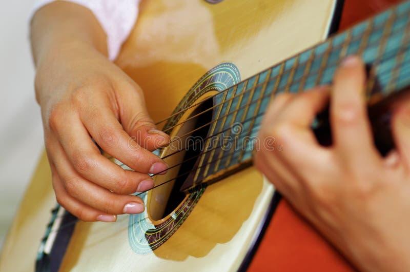 Guitarra acústica hermosa del primer que es jugada por la mujer hispánica que se sienta, concepto del músico imagen de archivo