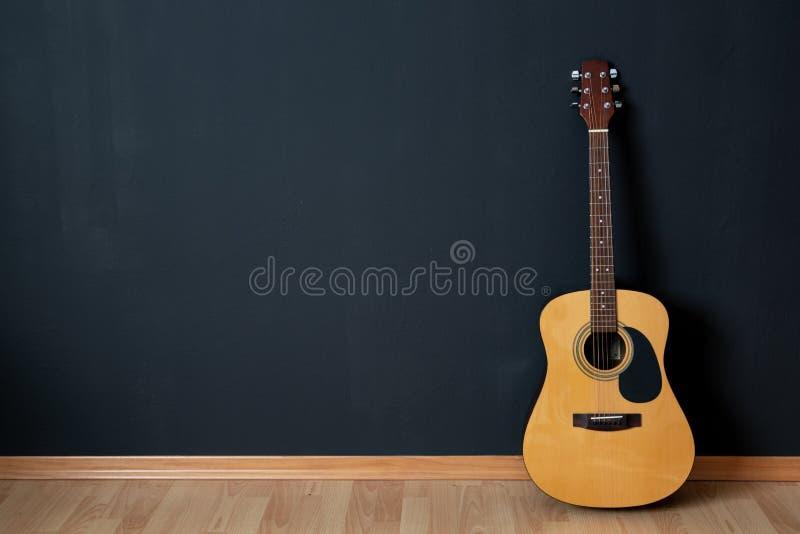 Guitarra acústica na sala vazia imagens de stock