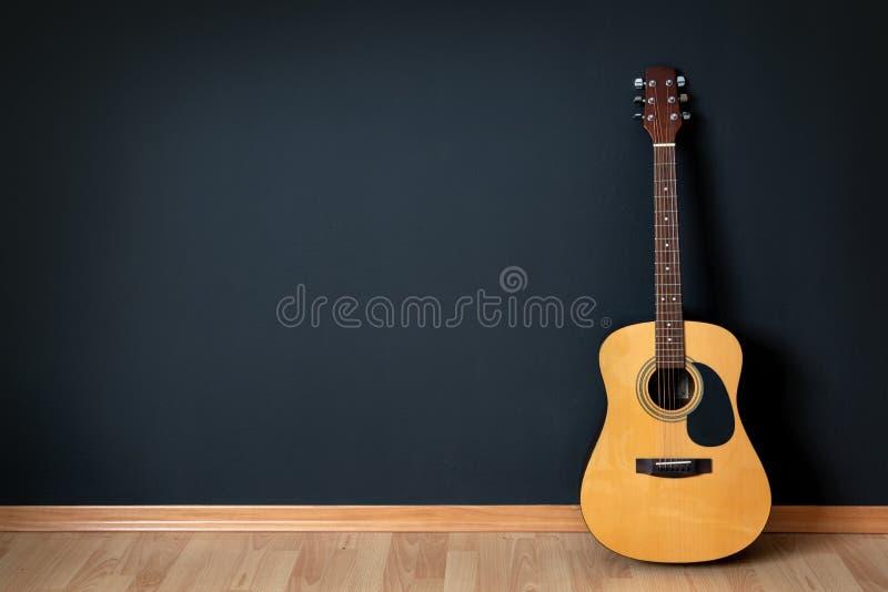 Guitarra acústica na sala vazia fotos de stock royalty free