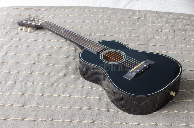 Guitarra acústica negra en cama fotografía de archivo